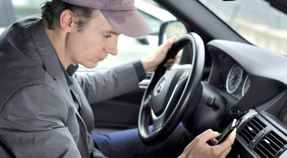 hombre usando celular en su automóvil