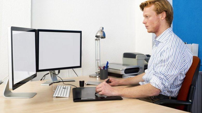 Persona trabajando con dos monitores